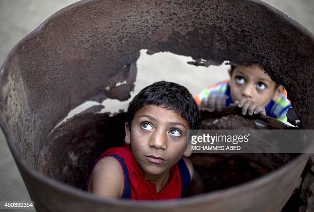 Palestinian boys play in a barrel outside their home in Beit Lahia in the northern of Gaza Strip on June 10 2014 Some 16 million Palestinians live in...