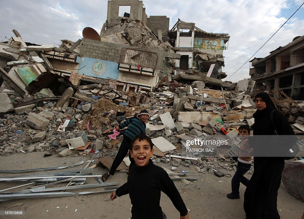 Palestinian boys play in the rubble of a house in Gaza City on November 27, 2012. AFP PHOTO / PATRICK BAZ