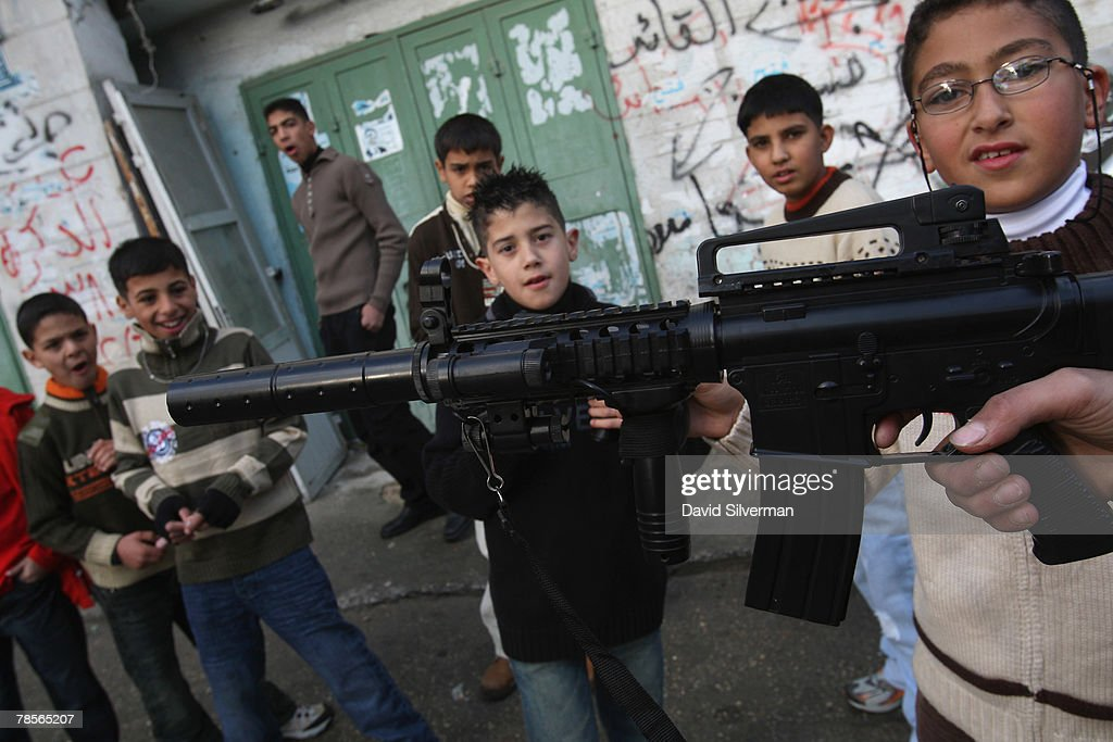 Palestinian boys play with their new toy guns, which are popular presents for Eid al-Adha, in al-Azza refugee camp December 19, 2007 in Bethlehem in the West Bank. The biblical town is celebrating both Christmas and the Muslim Feast of the Sacrifice over the next week.