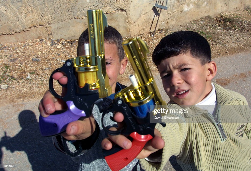 Palestinian boys play with their new toy pistols December 16, 2001 in the West Bank town of Ramallah, which they received as gifts for the Muslim feast of Eid al-Fitr. Eid al-Fitr is a three day celebration at the end of the fasting month of Ramadan. In a televised speech to his people, Palestinian leader Yasser Arafat called for a stop to armed and suicide attacks against Israelis.