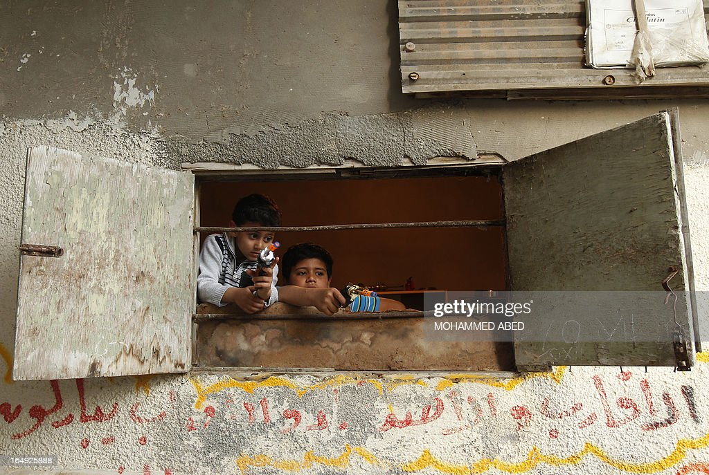 Palestinian boys play with toy guns by the window of a house in the Shati refugee camp in Gaza City on March 29, 2013. Palestinians mark Land Day on March 30 to commemorate the death of six Arab Israeli protesters at the hands of Israeli troops during mass protests in 1976 against plans to confiscate land in Galilee.