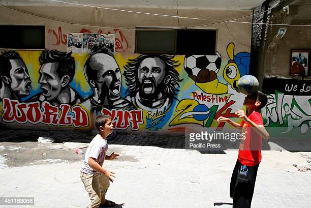Palestinian boys plays with a ball in front of a graffiti wall in the Khan Yunis refugee camp in the southern Gaza Strip depicting football players...