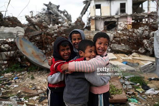 Palestinian boys pose for a picture next to the debris of a building that was destroyed during the 50day war between Israel and Hamasled militants in...