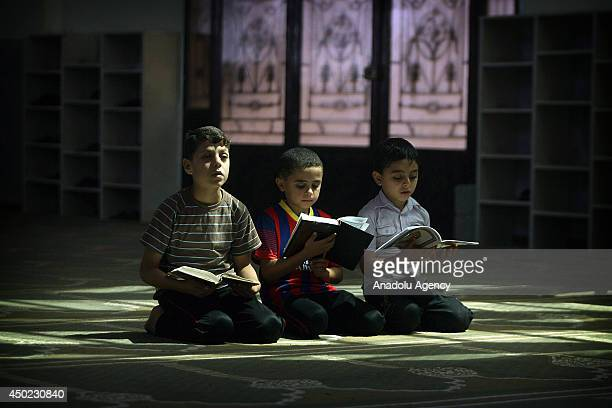 Palestinian boys read verses from the Quran at a mosque during a summer camp for the study of Islam's holy book organized by Hamas in Rafah in the...