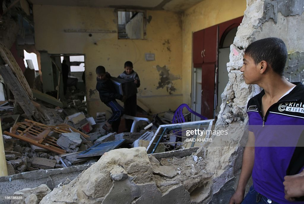 Palestinian boys remove salvageable items from a damaged house following overnight Israeli air strikes in the southern Gaza Strip town of Rafah on November 20, 2012. The Israeli military said it attacked about 100 targets in the coastal strip during the night, using aircraft, warships and artillery. AFP PHOTO/ SAID KHATIB