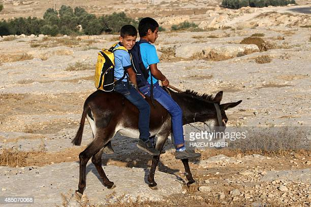 Palestinian boys ride a donkey to go to school on the first day of the new school year on August 24 2015 in the West Bank village of Susya southeast...