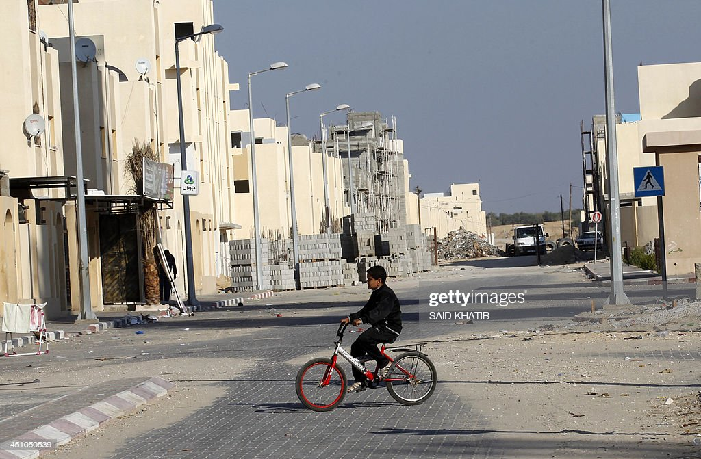 A Palestinian boys rides a bicycle near building materials on the street outside new houses which are part of a project funded by the United Nations Relief and Works Agency for Palestine Refugees (UNRWA) in the southern Gaza Strip town of Rafah on November 21, 2013. The UNRWA, which is facing a 36-million dollar deficit, halted 19 out of 20 construction projects in the Hamas-controlled Gaza territory after Israel suspended the entry of all construction materials into Gaza following the discovery of a tunnel by Israeli authorities from the besieged strip into Israel in October.