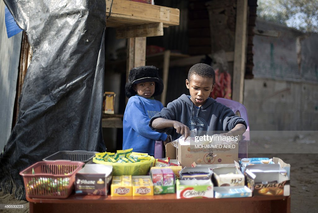 Palestinian boys sell candy outside their house in Biet Hanun northern Gaza Strip, on November 19, 2013. The Hamas run Palestinian territory is suffering a shortage in butane gas. AFP PHOTO/MOHAMMED ABED