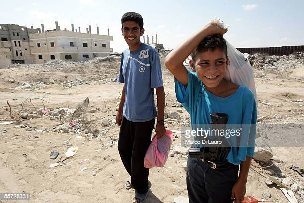 Palestinian boys smile as one carries a toy gun in his pants September 19 2005 in Rafah refugee camp Gaza Strip Several Palestinian families who had...