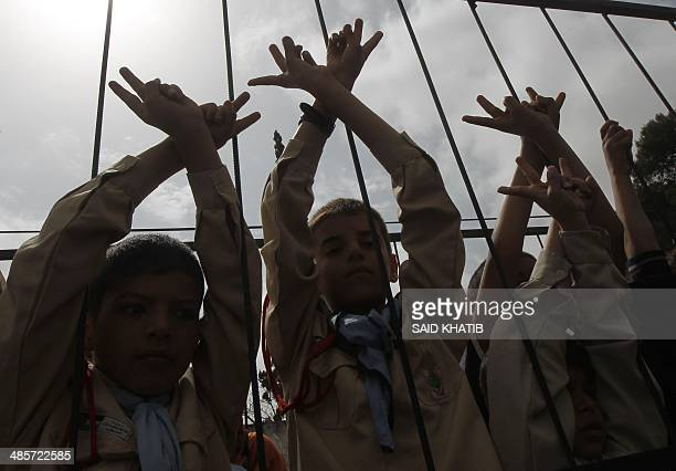 Palestinian boys stand behind mock jail bars during a rally calling for the release of Palestinian prisoners from Israeli jails in Rafah in the...