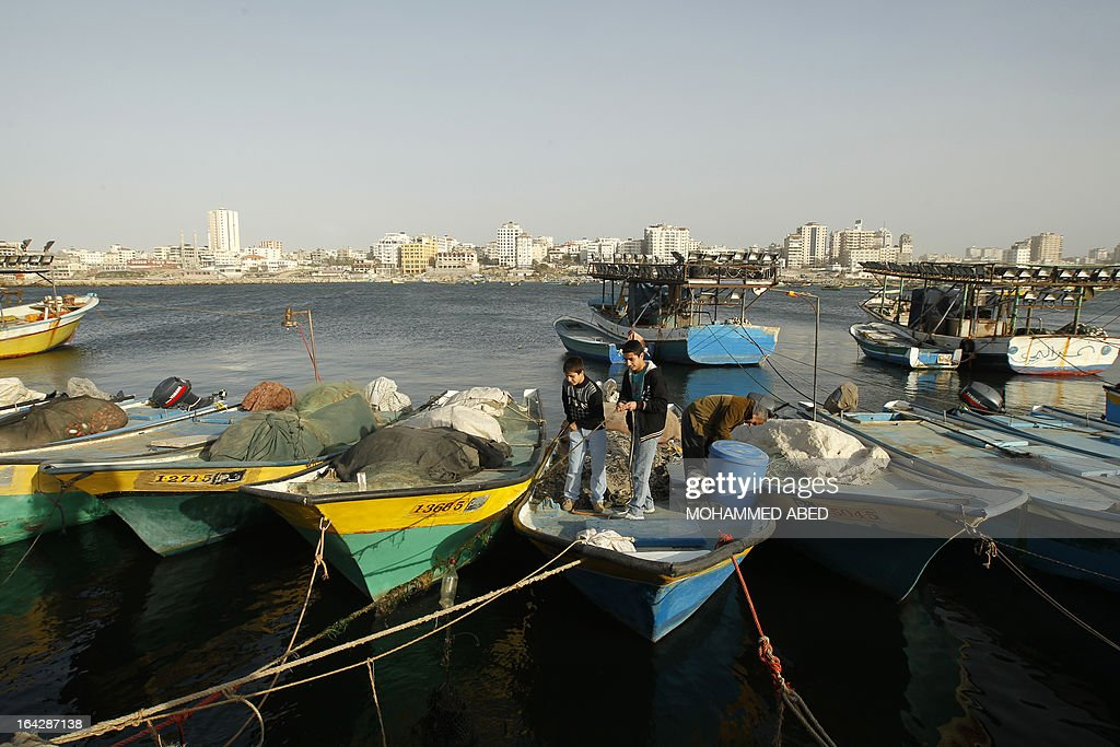 Palestinian boys stand on a fishing boat at the port of Gaza City on March 22, 2013. Israel cut the distance from the shore that Gaza fishermen are allowed to sail from six to three miles and shut the Kerem Shalom goods crossing from Israel into the Gaza Strip in response to a rocket attack against southern Israel.