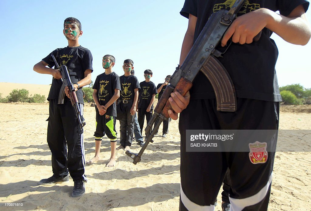 Palestinian boys take part in a military-style summer camp being held by the Islamic Jihad movement during the youngsters' summer school vacation in Rafah town, in the southern Gaza Strip, on June 12, 2013. Thousands of youngsters between the age of six and 16, can participate in the summer camp where they receive military as well as religious training.