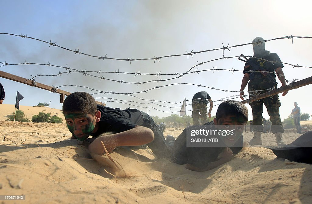 Palestinian boys take part in a military-style summer camp being held by the Islamic Jihad movement during the youngsters' summer school vacation in Rafah town, in the southern Gaza Strip, on June 12, 2013. Thousands of youngsters between the age of six and 16, can participate in the summer camp where they receive military as well as religious training. AFP PHOTO/ SAID KHATIB