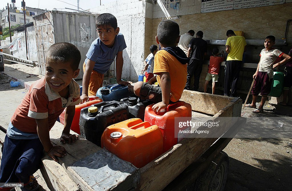 Palestinian boys wait on a cart to fill his bottles with water from a public tap in Rafah, Gaza strip due to the water shortage caused by Israeli attacks in Gaza on August 28, 2014.