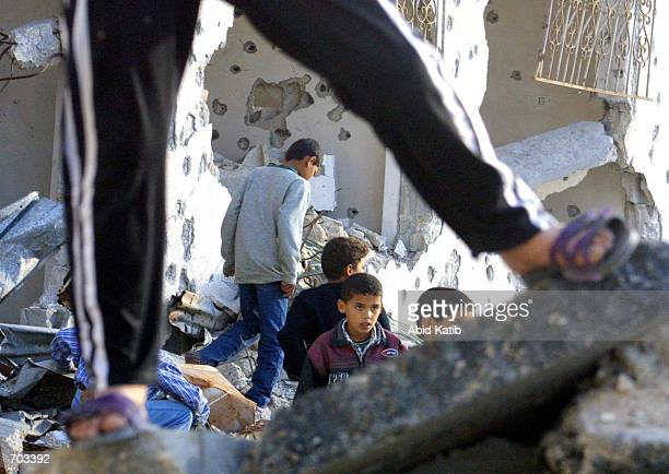 Palestinian boys walk through buildings February 27 2002 destroyed during recent clashes with Israeli troops along the border with Gush Katif Jewish...