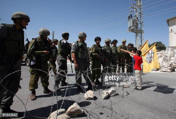Palestinian boys wave the Fatah party flag in front of Israeli soldiers standing guard during a protest against Israel's controversial separation...