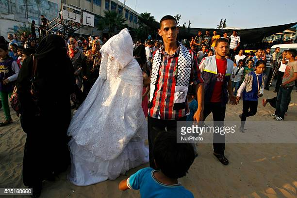Palestinian bride and her groom who each lost his home during fighting between Hamas and Israel pose for a picture during their wedding ceremony...