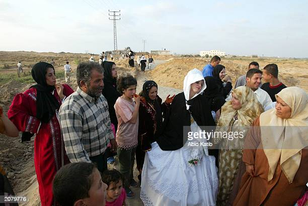 Palestinian bride Houda Abu Wadi walks with her relatives through a twokilometer dirt road June 13 2003 located on a beach in order to avoid an...