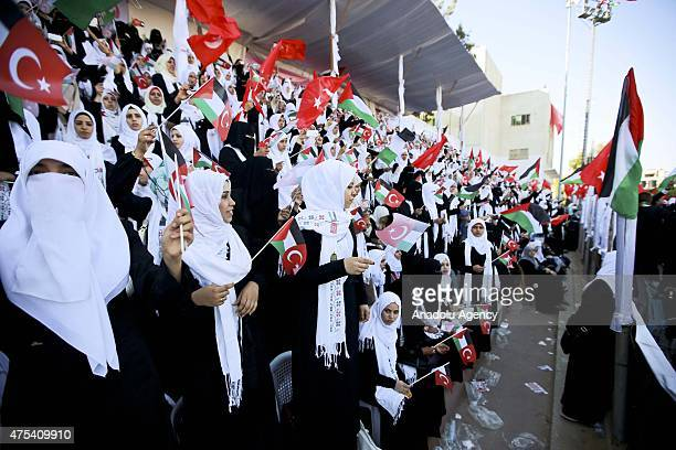 Palestinian brides wave Palestinian and Turkish national flags during a mass wedding ceremony at the Yarmouk Stadium in Gaza on May 31 2015 Two...
