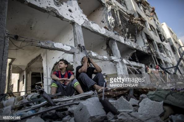 Palestinian brothers sit on the rubble of their house in front of an apartment block in part of the northern Beit Hanun district of the Gaza Strip...