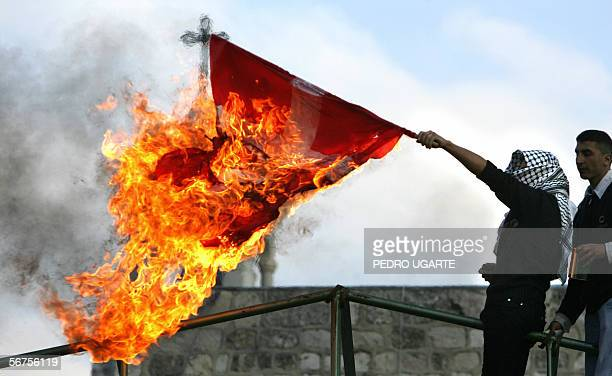 Palestinian burns a Danish flag in the West Bank city of Bethlehem 06 February 2006 during a demonstration against the publication of cartoons...