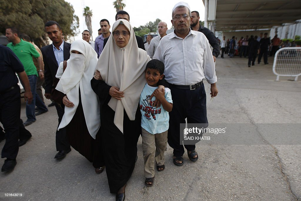 Palestinian cancer patient Wafa Dahshan (C), who was detained with her husband aboard the Gaza-bound flotilla raided by Israel on May 31, 2010, walks with her son and other family members upon her arrival in the southern Gaza Strip town of Rafah through at the border crossing with Egypt on June 5, 2010, after being deported by the Israeli authorities to Turkey where she was receiveing treatment.