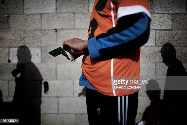 A Palestinian candidate arranges his ID card into his wallet while waiting for a physical test at a Hamas police recruitment center in Gaza City on...