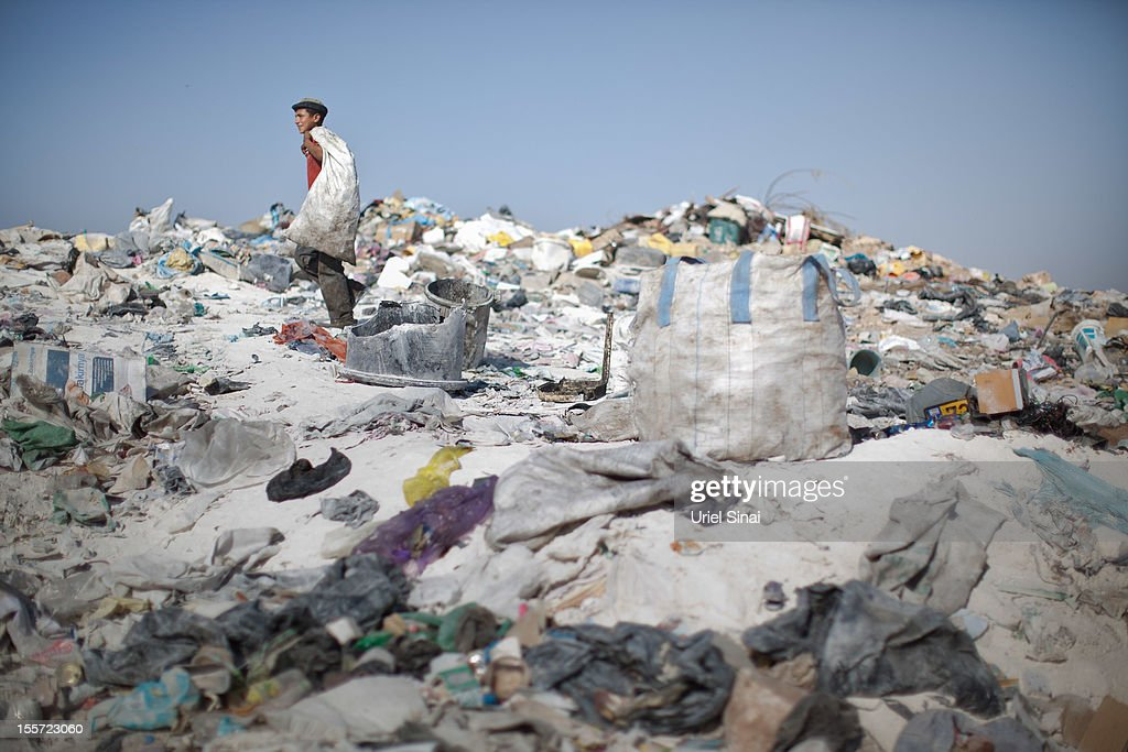 A Palestinian carries a bag as he sifts through a garbage dump on November 7, 2012 south of Hebron, West Bank. About 40 Palestinain men and children work at the West Bank garbage dump looking for clothing, metal and wood discarded, in large part, from the Jewish settelment in the region.