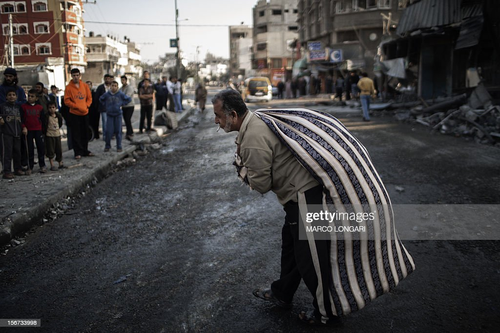A Palestinian carries a bag of salvaged items from a house destroyed in an Israeli airstrike on Gaza City, on November 20, 2012. Seven Palestinians were wounded in strikes on Gaza overnight, but no one was killed in the first night without fatalities since the Israeli air campaign began nearly a week ago.