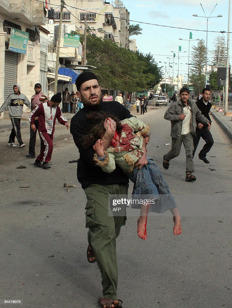 A Palestinian carries a wounded girl following an Israeli air strike in Gaza city on January 1, 2009. Israel killed a top Hamas commander on Thursday in the biggest blow yet against the Islamist leadership as dozens more air strikes on Gaza took the death toll from the six-day blitz above 400. AFP PHOTO/MOHAMMED AL-ZAANOUN