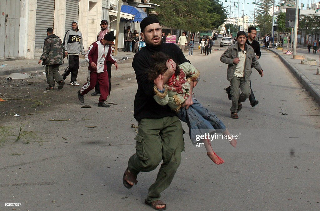 A Palestinian carries a wounded girl following an Israeli air strike in Gaza city on January 1, 2009. Israel killed a top Hamas commander on Thursday in the biggest blow yet against the Islamist leadership as dozens more air strikes on Gaza took the death toll from the six-day blitz above 400.
