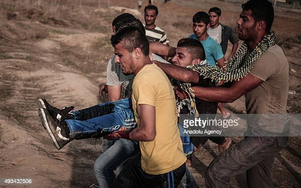 Palestinian carry an injured protester during a demonstration against Israeli Government's violations at AlAqsa Mosque on October 20 2015 near...