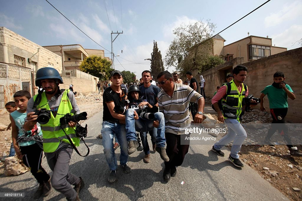 Palestinian carry Palestinian journalist Ahmed Talat wounded by Israeli forces' attack during a demonstration after the Friday Prayer against Israeli...
