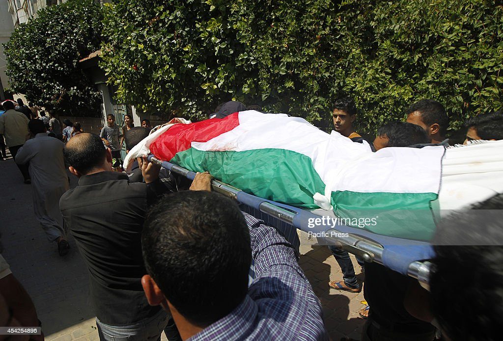Palestinian carry the bodies of two Palestinian brothers Omar ,16, and Mohammed,12, Braim who were killed yesterday, before the open-ended ceasefire in the Gaza war between Israel and the Palestinians held on Wednesday in Khan Younis in southern Gaza strip.