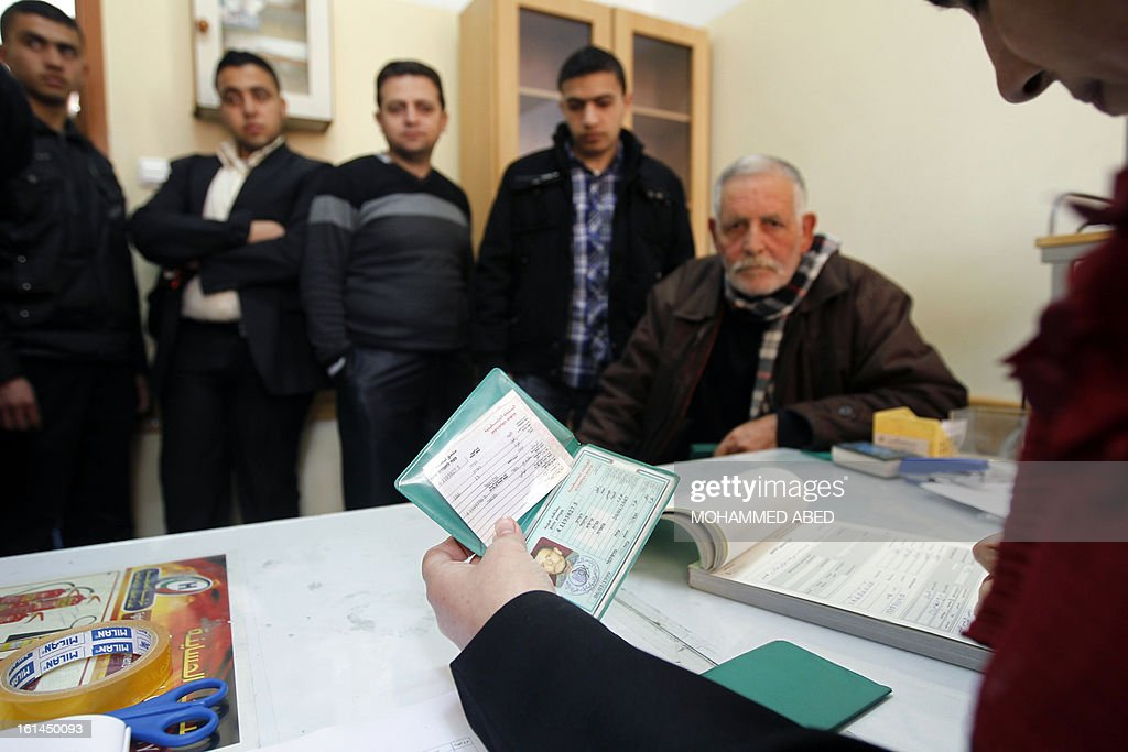 A Palestinian Central Election employee checks a voter card at a Central Election Commission office in Gaza City on February 11, 2013. Palestinian electoral officials began the long-overdue process of updating voter rolls in the West Bank and Gaza in a vital step towards eventual elections. AFP PHOTO/MOHAMMED ABED