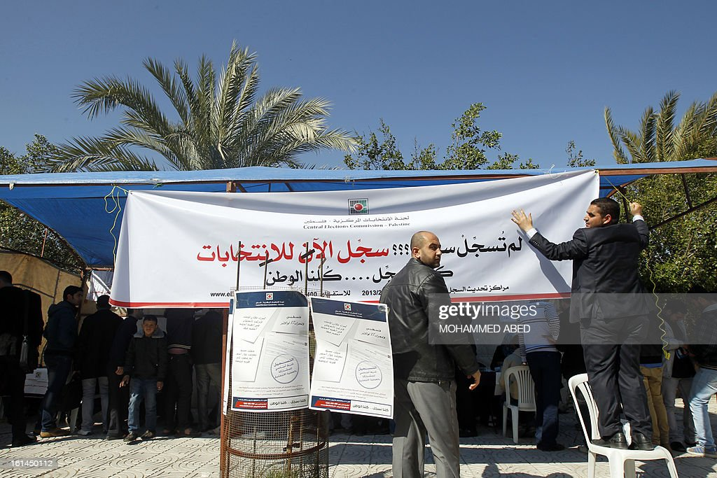 A Palestinian Central Election employee erects a placard in front of a Central Election Commission office in Gaza City on February 11, 2013. Palestinian electoral officials began the long-overdue process of updating voter rolls in the West Bank and Gaza in a vital step towards eventual elections.
