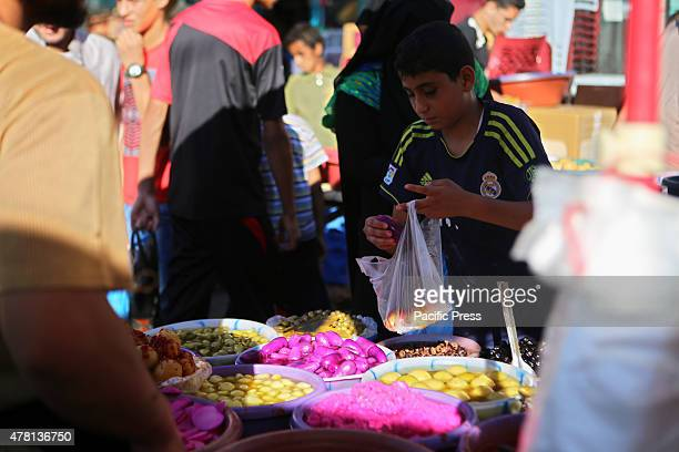 Palestinian child buy the pickles in a street market on the fifth day of the holy month of Ramadan in Rafah in the southern Gaza Strip