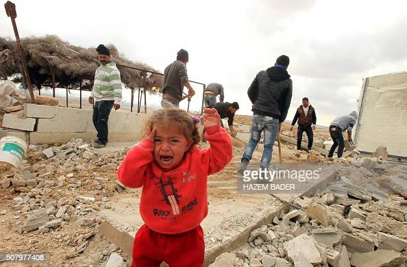 A Palestinian child cries as Palestinians salvage items from their home after it was demolished by Israeli bulldozers in the area of Musafir Jenbah...