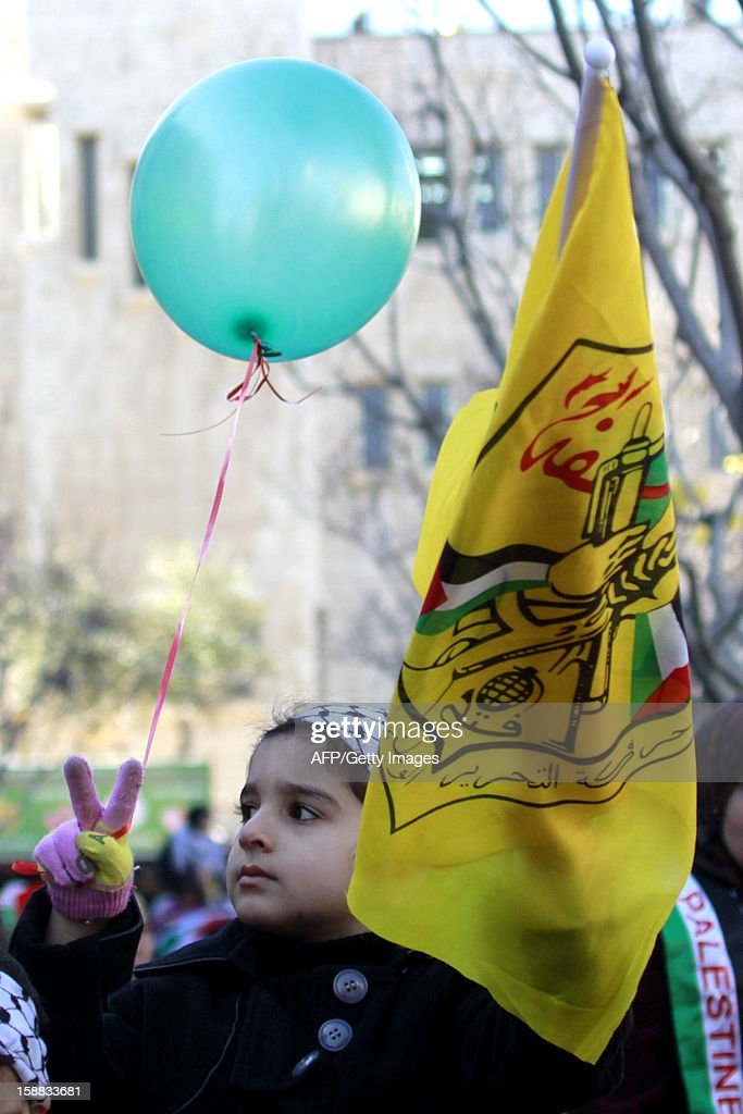 A Palestinian child flashes the V-sign for victory as she holds the Fatah movement flag amid supporters of Palestinian leader Mahmud Abbas in front of the Church of the Nativity in the West Bank city of Bethlehem, on December 31, 2012, during celebrations marking the 48th anniversary of the movement's founding.