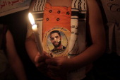A Palestinian child holds a candle during rally in solidarity with Palestinian football player Mahmoud Sarsak who has been held in Israeli jail since...