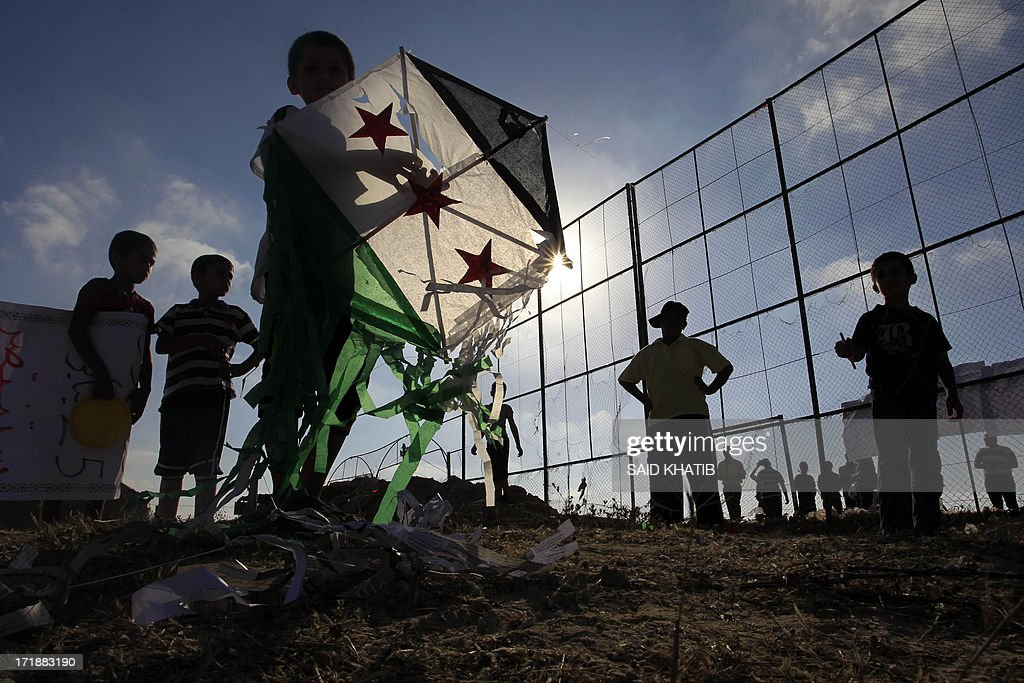 A Palestinian child holds a kite bearing Syria's former independence flag which has been adopted by the rebels forces fighting agianst Syrian pro-government forces in Syria in solidarity with the country during an event organised by Hamas in Rafah town, in the southern Gaza Strip on June 29, 2013.