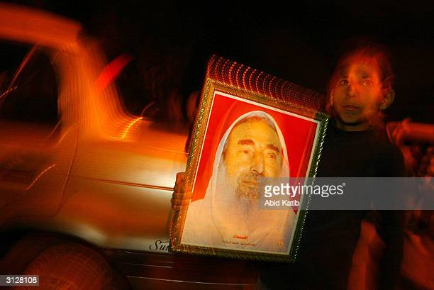 Palestinian child holds a poster of assasinated Hamas leader Sheikh Ahmed Yassin as he participates in a night rally of the militant wing of Hamas on...