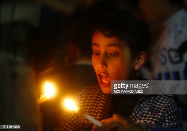 A Palestinian child holds candles during a rally to demand a beeter access to electricity in the Gaza Strip on April 14 2016 in Gaza City / AFP /...