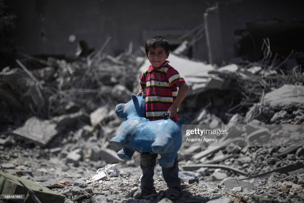 A Palestinian child holds his toy around the ruins as he collects his usable belongings following a 72-hour humanitarian ceasefire in Beit Hanoun, Gaza on August 11, 2014.