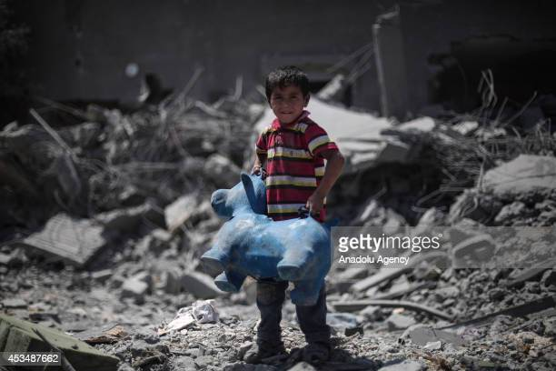 Palestinian child holds his toy around the ruins as he collects his usable belongings following a 72hour humanitarian ceasefire in Beit Hanoun Gaza...