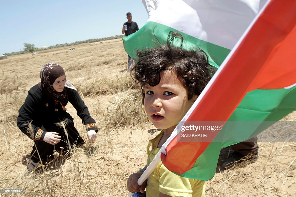A Palestinian child holds the national flag during a rally to commemorate Nakba day ahead of the wheat harvest near the border between Israel and Rafah in the southern Gaza Strip on May 14, 2013. Palestinians and Arab Israelis are preparing to mark Nakba Day on May 15 which commemorates the exodus of hundreds of thousands of their kin after the establishment of Israel state in 1948.