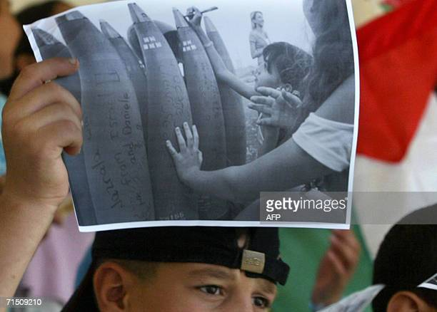 Palestinian child holdsup a poster showing an Israeli child writing on rockets being fired into Lebanon by the Israeli army during a rally at the...