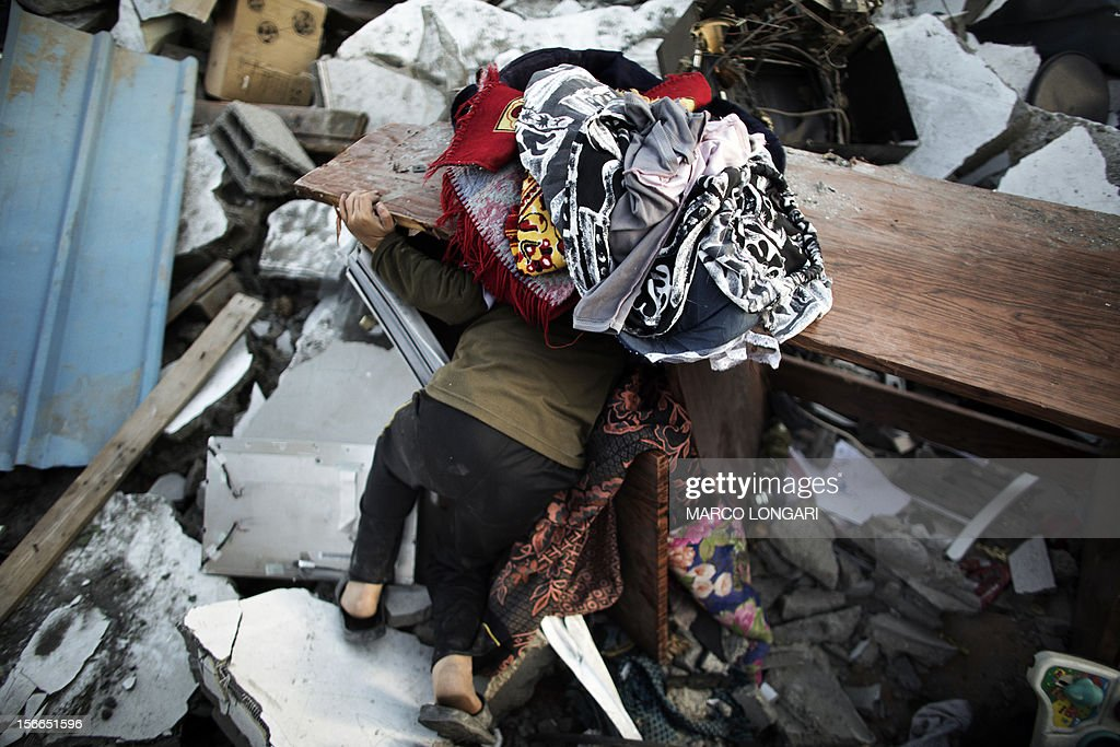 A Palestinian child looks for his belongings under the rubble of his house following overnight Israeli air strikes on the village of Beit Lahia in the northern Gaza Strip on November 18, 2012. Israeli war planes hit a Gaza City media centre and homes in northern Gaza in the early morning, as the death toll mounted, despite suggestions from Egypt's President Mohamed Morsi that there could be a 'ceasefire soon.'