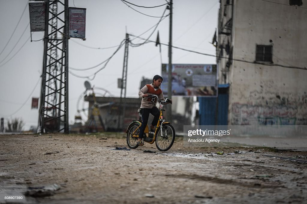 Palestinian child rides bicycle during heavy rain, in Gaza City, Gaza on February 7, 2016.