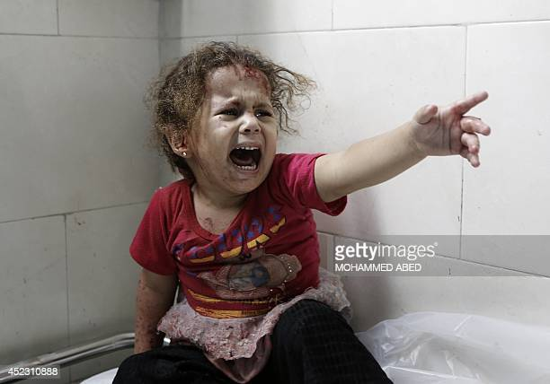 A Palestinian child shouts at alShifa hospital after Israeli forces shelled her house in Gaza City on July 18 2014 Israel began a ground operation in...